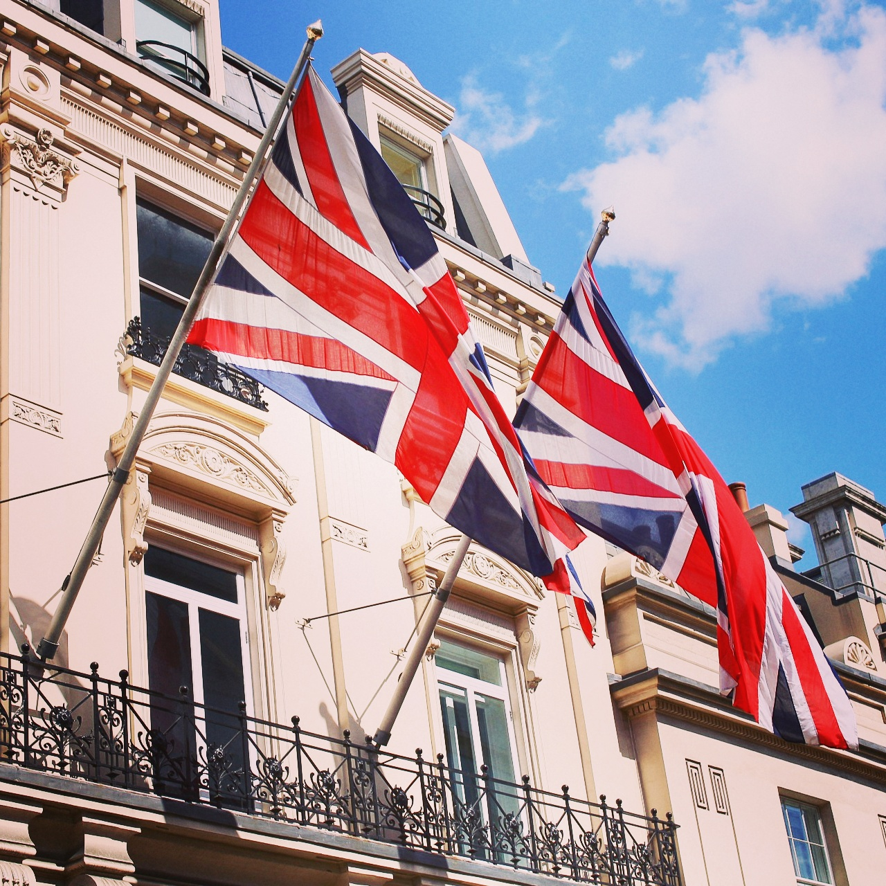 Waving Union Jack flags from the Ritz facade in London