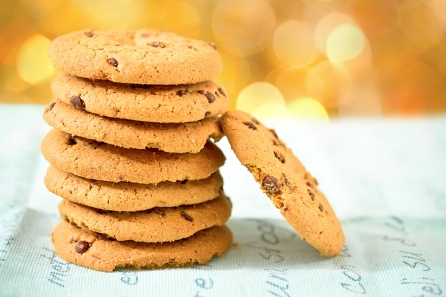 chocolate chip cookies on blue table set with bokeh background