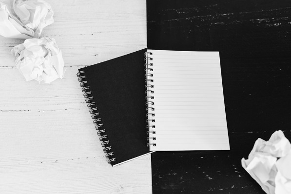 black and white notepads on opposite coor surface facing each other, contrasty minimalist flatlay