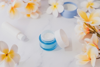 spa and skincare treatments concept, moisturiser scrub and hand cream pots on marble table with exotic frangipani flowers