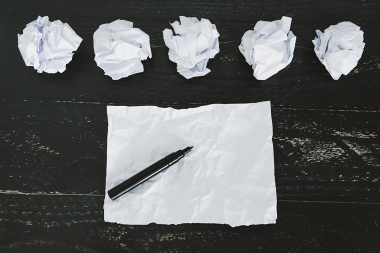 concept of drafting documents and struggling to write a text, set of scrunched paper balls and empty torn sheet on dark moody background