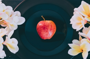 one apple on black plate on dark background and white flowers around it, concept of choosing the best organic products