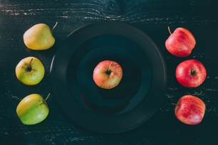 one apple on black plate on dark background and others both green and red outside the dish, concept of choosing the best organic products