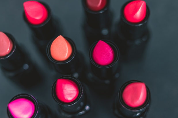 group of red pink and nude lipsticks with different colors and textures on dark table, close-up shot with shallow depth of field