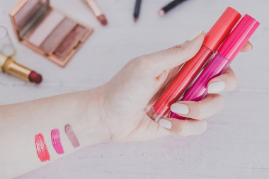 woman's hand holding lipgloss product and testing it surrounded by other make-up items on desk, concept of beauty industry