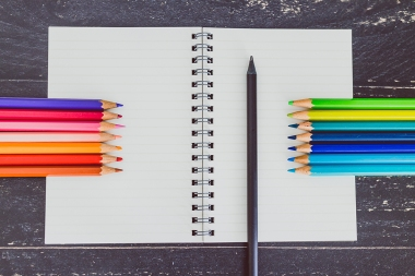 desk with notepad and colourful pencils with empty pages and copyspace, concept of creativity and inspiration