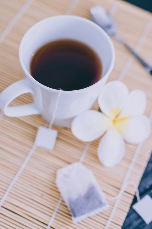 cup of dark tea on bamboo placemat with spoon and flowers all around, concept of detox or relaxing habits