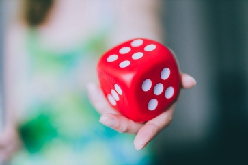 girl handing big red dice shot at shallow depth of field, concept of trying your chance at a game