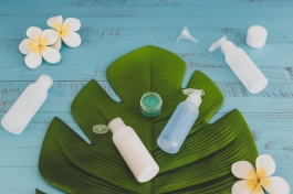 beauty industry concept: organic lotions and skincare products with tropical flowers and leaf in spa setting