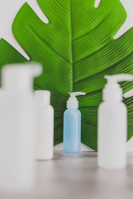 beauty industry concept: organic lotion isolated from a group of other skincare products with tropical leaf in the background