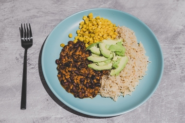 vegan recipes concept: mexican style dish with spicy black bean coconut rice corn and avocado topping