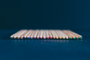 set of coloured pencils on desk on dark background shot at shallow deph of field, concept of art and craft projects