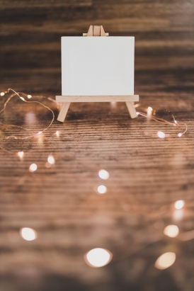 black canvas miniature surrounded by fairy lights on wooden desk, background shot with copyspace to add your text