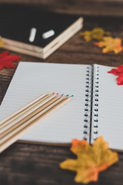 back to school tabletop arrangement with coloured pencils notepad and mixed stationery items among autumn leaves, concept of new school year