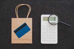 shopping bag with calculator and payment card and magnifying glass analyzing it, customer spending habits concept