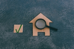 buying or moving house concept, miniature cardboard house with magnifying glass analyzing it