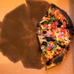 enjoyable healthy food concept, half eaten vegetarian woodfire pizza in cardboard box on wooden table setting