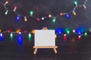 blank canvas miniature with multicolor festive string lights bokeh and copyspace to add your text