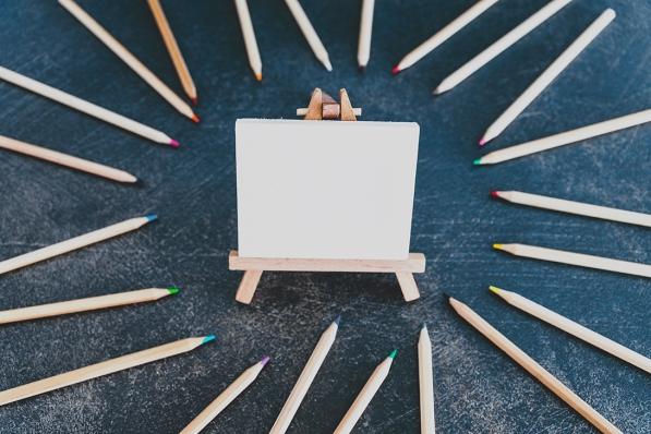 creativity and education concept, assortment of coloured pencils surrounding miniature blank canvas on dark desk