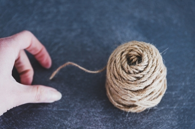 woman's hand untangling ball of thread by pulling string, complex of solving chaotic situations