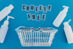 vegan beauty products against animal testing conceptual still-life, shopping basket and mixed lotion bottles with Cruelty Free text and leaves metaphor of ethically sourced natural ingredients